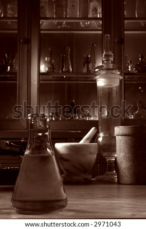 Vintage glassware and old pharmacy equipment in antique science research lab with apothecary style medicine case filled with ancient medical glass vials in nostalgic vintage sepia - stock photo