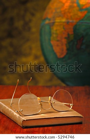 Vintage globe behind a wood desk with a pair of glasses on an old book - stock photo