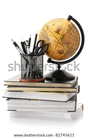 Vintage globe on stack of books and office supplies isolated against white background.