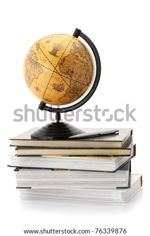 Vintage globe on stack of books isolated against white background.