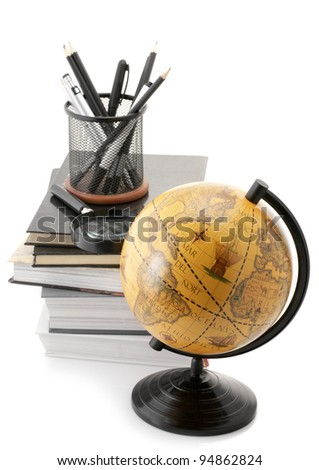 Vintage globe, stack of books and office supplies isolated on white background.
