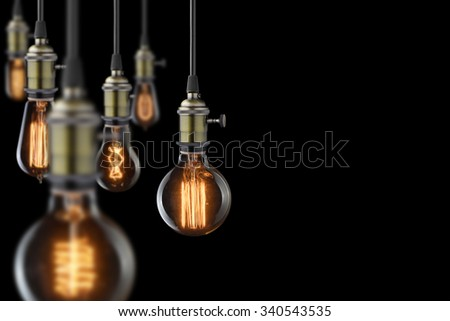 vintage glowing light bulbs on black background - stock photo
