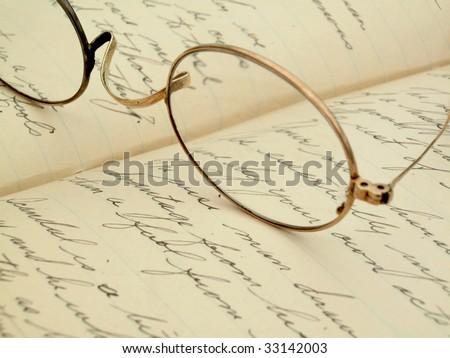Vintage gold eyeglasses on hand written diary - stock photo