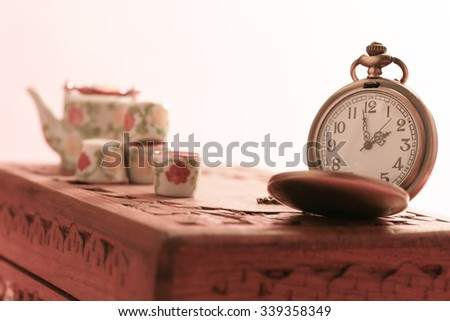 vintage gold pocket watch with old wooden box and mini tea set - stock photo
