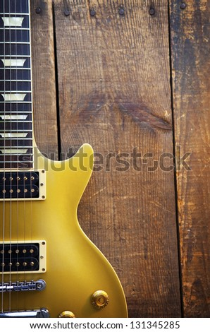 Vintage Gold top guitar on old wood surface. - stock photo