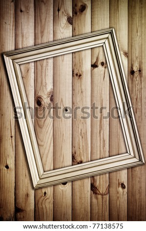vintage golden frame on wooden background with artistic shadows added - stock photo