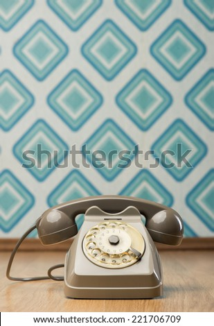 Vintage gray telephone on hardwood floor, diamond light blue retro wallpaper on background. - stock photo