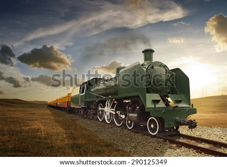 vintage green and yellow steam powered railway train - stock photo