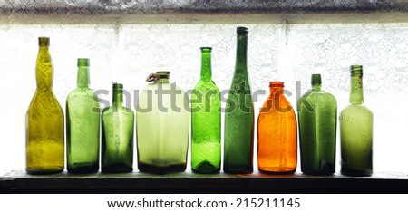 Vintage green bottles with one brown on windowsill in daylight - stock photo