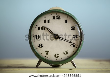 Vintage green clock against a blue background