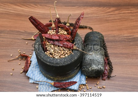 Vintage Grinding stone / stone blender and pestle for grinding spice Kerala, India. Coriander seeds and dry red chilies pepper in a Stone mortar. aromatic Indian spices scattered, curry masala - stock photo