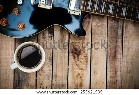 Vintage guitar and coffee on old wooden texture - stock photo