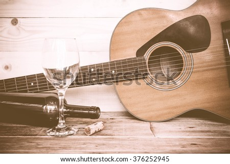 vintage Guitar with wine bottle and glass on the old wood floor. - stock photo