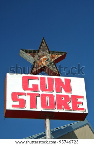 Vintage Gun Store Sign with Blue Sky