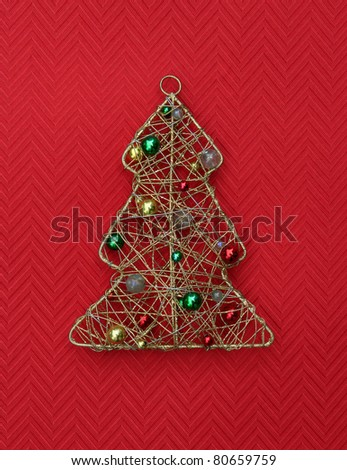 Vintage Handmade Christmas Tree Ornament with Colorful Beads isolated on red background - stock photo