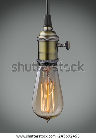 Vintage hanging light bulb over gray background  - stock photo