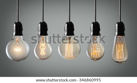 Vintage hanging light bulbs over gray background  - stock photo