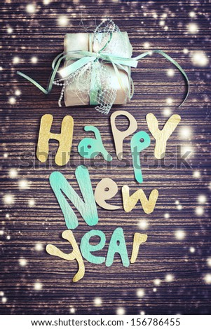 Vintage Happy New Year background.Happy New Year lettering with the gift on wooden background. - stock photo