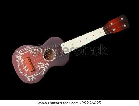 Vintage hawaii ukulele guitar isolated against black background - stock photo