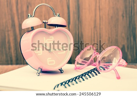 Vintage heart shape alarm clock with chic eye glasses on open notebook. With wood background. Retro filter. - stock photo