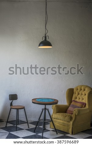 Vintage hipster loft interior with yellow armchair and an iron stool