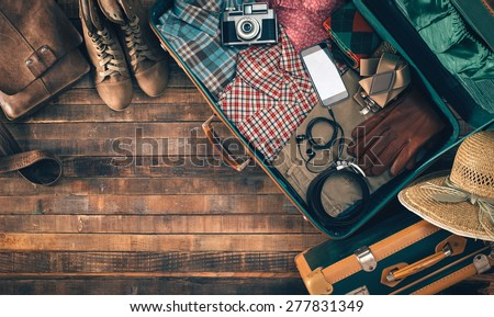 Vintage hipster suitcase packing before leaving with old suitcase, camera and accessories on a wooden table, top view - stock photo