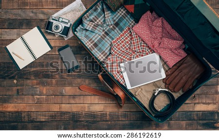 Vintage hipster traveler packing, open suitcase on a wooden table with clothing, camera and mobile phone, top view - stock photo