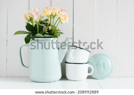 Vintage home arrangement, summer flowers and enamelware on a barn wall background, soft pastel colors. - stock photo
