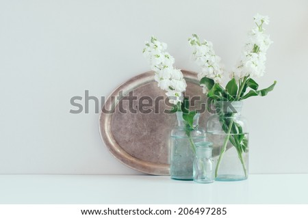 Vintage home decor, white matthiola flowers in different blue glass bottles vases and an antique silver tray on a shelf by the wall - stock photo
