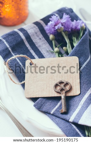 Vintage home table setting with blue napkins, antique cutlery and purple cornflowers on white wooden table. Blank cardboard tag and an old key - stock photo
