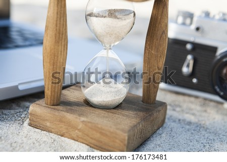 Vintage hourglass with silver laptop and old camera in the sand at the beach - stock photo