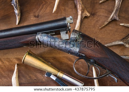 Vintage hunting gun, a lot of antlers, hunting horn on a wooden background. Close up