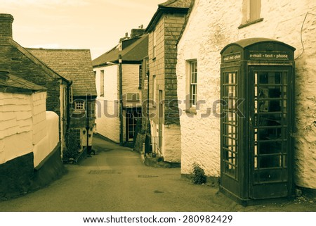 Vintage image back lane in Port Isaac, Cornwall with old fashioned British phone booth with modern communication signs, email, text, phone. - stock photo