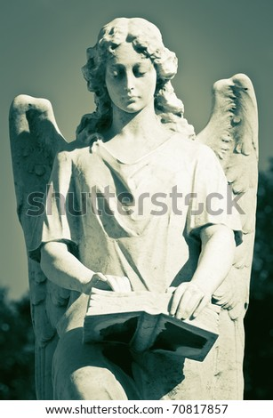 Vintage image of a beautiful angel reading a book - stock photo
