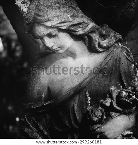 Vintage image of a sad angel on a cemetery against the background of leaves (details) - stock photo
