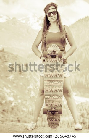 Vintage image of hippie young and beautiful girl with skateboard longboard, outdoor at mountain. She has a bandage on his forehead. - stock photo