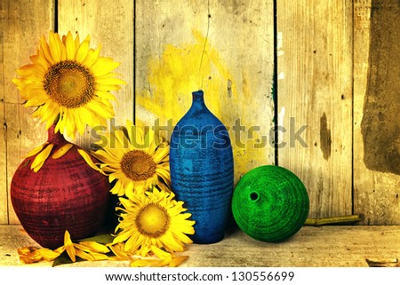 Vintage image of sunflowers and pottery with  a rustic wood planks background - stock photo