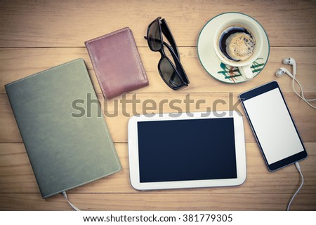 vintage image of tablet and smart phone with isolated screen and notebook paper on wooden table,business and technology concept