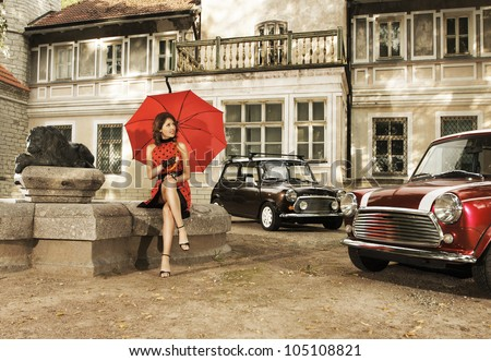 Vintage image of young attractive girl with two old cars - stock photo