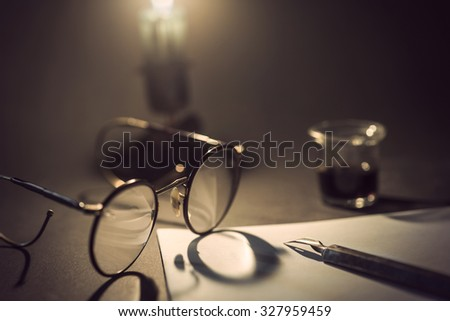 vintage ink pen on piece of white paper, old glasses with shadow from candle light and jar of ink in background