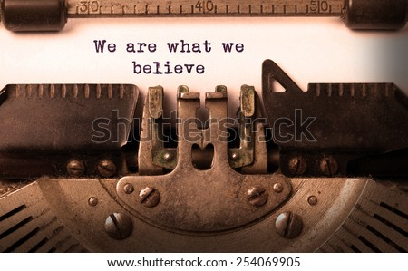 Vintage inscription made by old typewriter, we are what we believe - stock photo