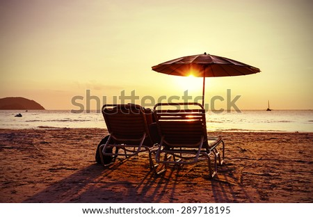 Vintage instagram stylized beach chairs and umbrella at sunset. Concept for holidays and relaxation. - stock photo