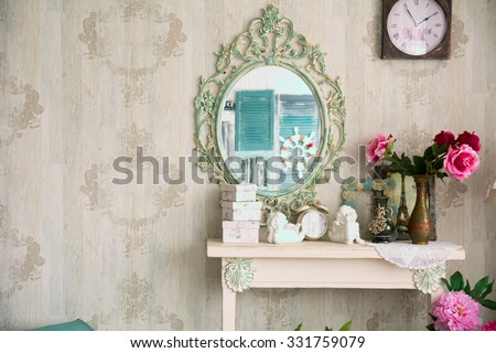 Vintage interior with mirror and a table with a vase and flovers. Designer wall clock. Angels on the table - stock photo