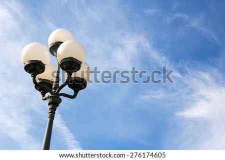 vintage iron lighting pole with lamp lantern on background of dark blue sky. - stock photo