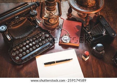 Vintage items, camera, pen, globe, clock, typewriter on the old desk - stock photo