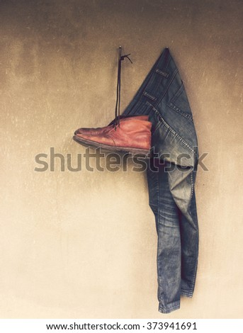 Vintage,Jeans and Leather shoes hanging on the wall - stock photo