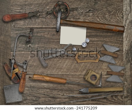 vintage jeweler tools and diamonds over wooden bench, blank card and name plate for your business - stock photo