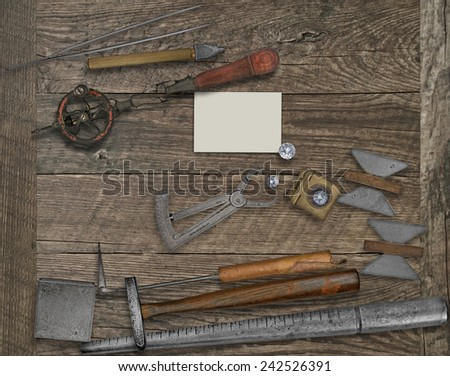 vintage jeweler tools and diamonds over wooden bench, blank card for your business - stock photo