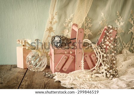 vintage jewelery, antique wooden jewelry box and perfume bottle on wooden table. filtered image  - stock photo