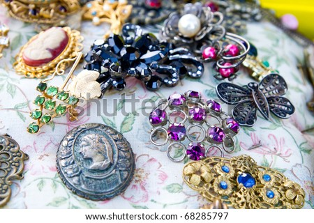 Vintage jewelry at the flea market (focus is on purple one, shallow dof) - stock photo